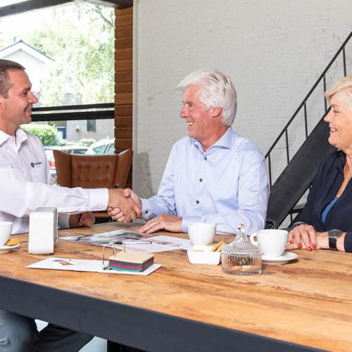 1100-woman-men-advisor-handshake-table-cu